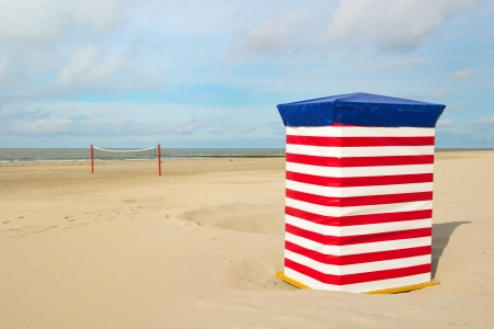 Beach of German wadden island with typical striped chair and volley ball net photo