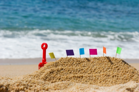 Sand castle with colorful flags at the beach photo