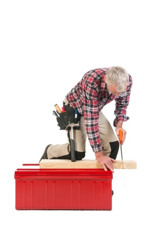 Senior man sawing as manual worker isolated over white background Stock Photo - 22115600