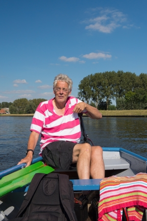 Elderly man in boat at the river
