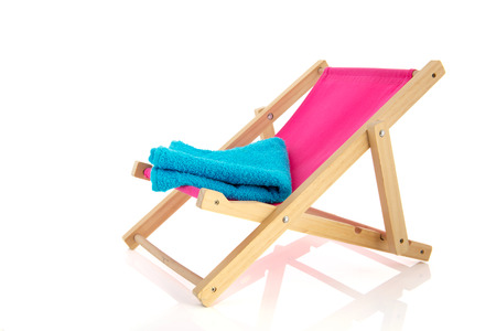 beach chairs: Pink beach chair with blue towel isolated over white background