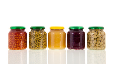 Row glass pots with canned vegetables isolated over white background Stock Photo