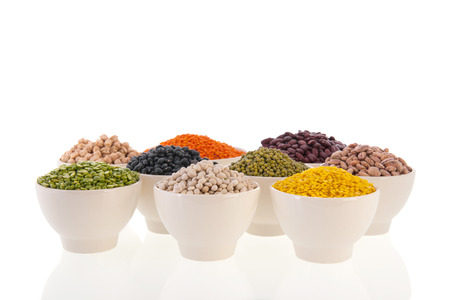 Assortment legumes in white bowls photo