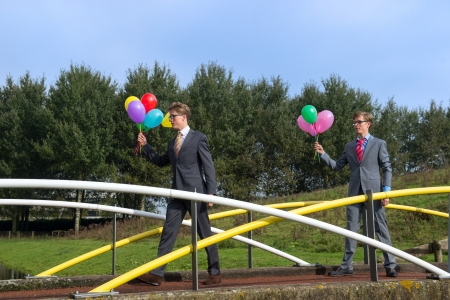 blowed: Business men outdoor with balloons on a bridge