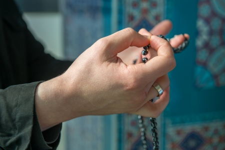 Islamic man praying with beads in the mosque photo