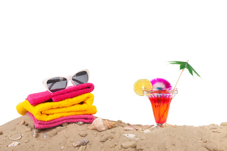 Beach sand with shells, towels and luxury cocktail isolated over white background photo
