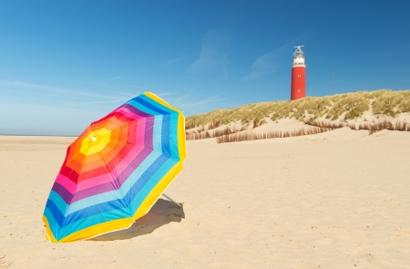 texel: lighthouse with colorful parasol in front on Dutch wadden island Texel Stock Photo