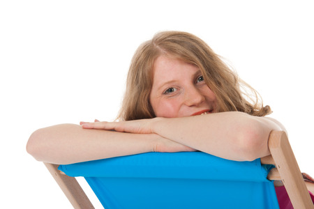 Blue beach chair with young woman for sun bath photo