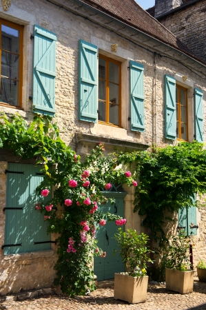 Typical French House With Roses And Blue Shutters Stock Photo