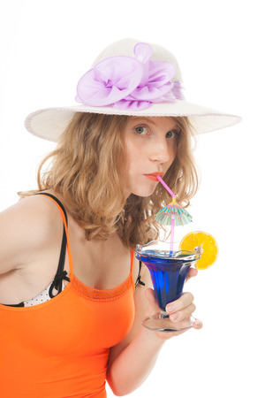 Young woman in bikini and orange singlet with blue cocktail at the beach photo