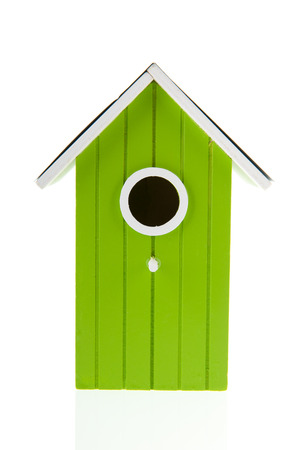 Green bird house with hole isolated over white background photo
