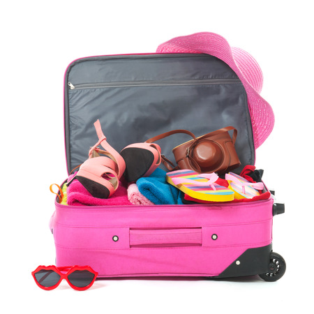 open suitcase: Packing the pink suitcase for the summer vacation Stock Photo