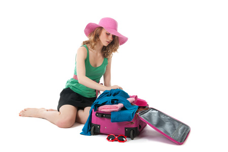 Packing the pink suitcase for the summer vacation by an young, blond woman photo