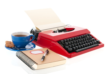 Vintage red typewriter with blank paper isolated over white background photo