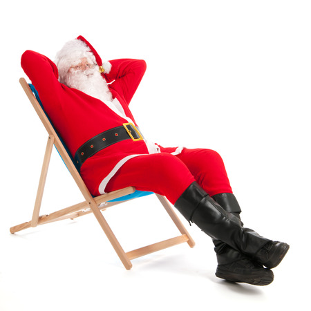 Santa Claus in beach chair on vacation isolated over white background