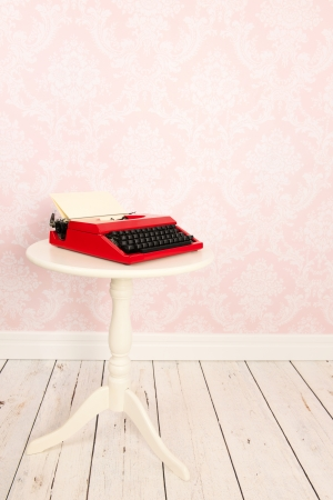 Vintage wall, wooden floor and plinth and old typewriter on table photo