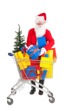Santa Claus putting a gift in shopping cart full luxury presents and tree photo