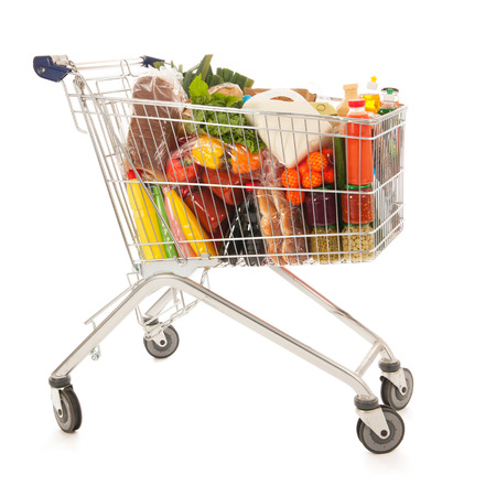 Shopping cart full with dairy grocery products isolated over white background Foto de archivo
