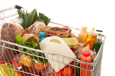 Shopping cart full with dairy grocery products isolated over white background Stockfoto