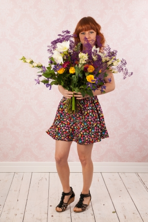 Woman in interior with colorful bouquet flowers photo