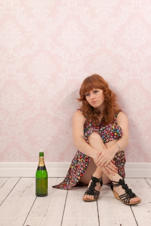 Sad woman with bottle wine sitting at the floor photo