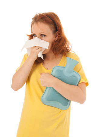 Red haired woman with yellow shirt blowing nose while holding hot water bottle isolated over white background photo