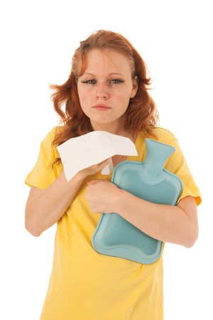 Red haired woman with yellow shirt blowing nose whle holding hot water bottle isolated over white background photo