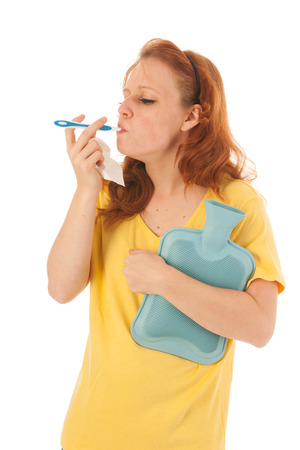 Red haired woman with yellow shirt with thermometer holding hot water bottle isolated over white background photo