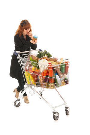 full shopping cart: Critical costumer reading label from groceries in supermarket