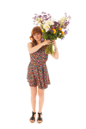 embarrassing: Attractive red haired girl standing with big bouquet flowers in windy studio isolated over white background