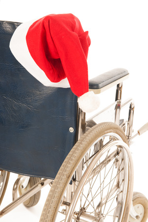 wheel chair with red hat Santa Claus isolated over white background photo