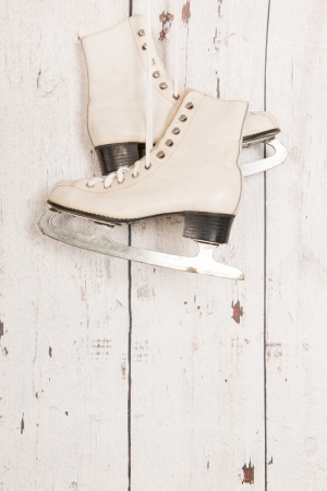 hanging ice skates on vintage wooden wall with copy space photo