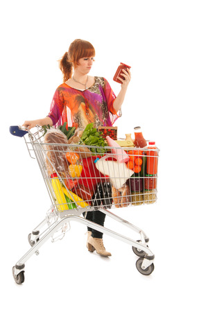 Woman with shopping cart full with dairy grocery products reading label  isolated over white background photo