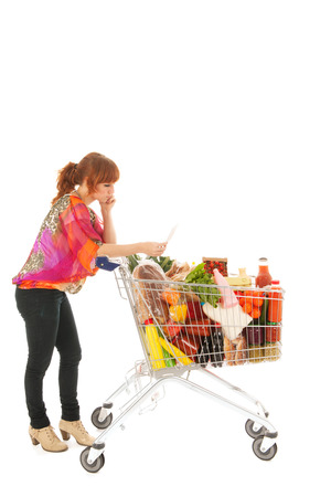 shopping list: Woman with shopping cart full with dairy grocery products reading list isolated over white background Stock Photo