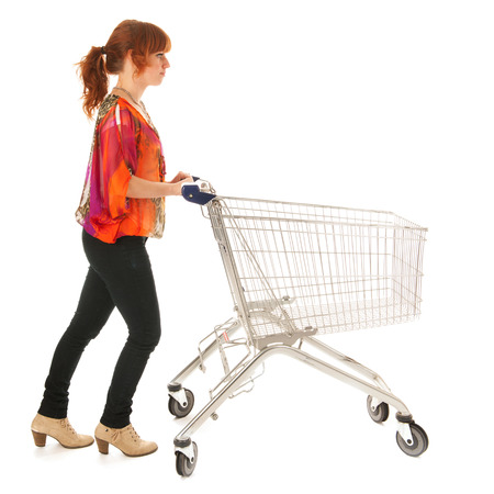 Red haired woman with empty shopping cart isolated over white background photo