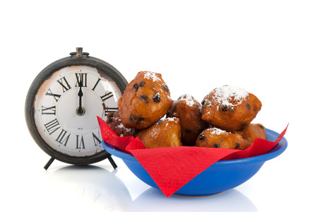 Dutch traditional oliebollen and watch on twelve oclock isolated over white