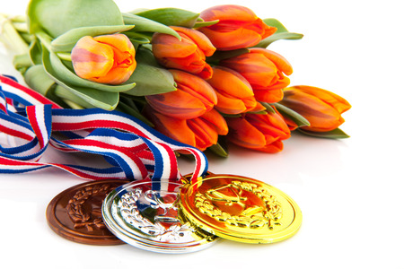 Dutch medals in gold, silver and bronze in front of orange tulips isolated over white  photo