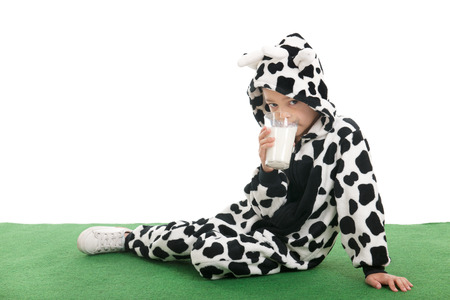 Little boy dressed as cow sitting in the grass and drinking milk photo