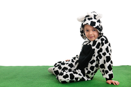 Little boy dressed as cow sitting in the grass photo