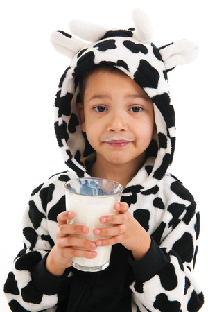 Little boy dressed as cow drinking healthy glass of milk photo