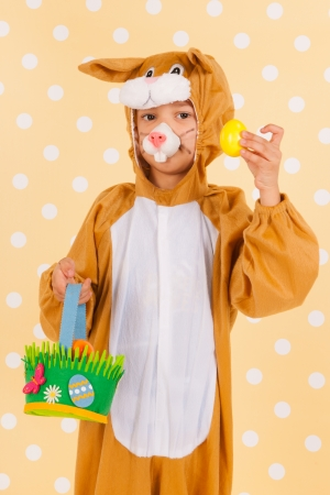 Little child as easter hare with basket full of colorful eggs photo