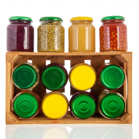 Wooden crate full with glass pots preserved vegetables photo