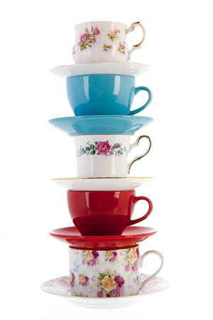 stacked vintage coffee or tea cups isolated over white background photo