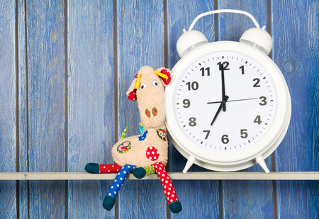 seven o'clock: Stuffed animal Giraffe sitting next to alarm clock at seven oclock isolated over white background