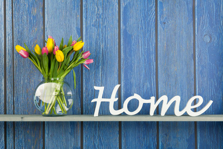 interior shelf: Home in white letters with colorful bouquet tulips in pink and yellow isolated on background Stock Photo
