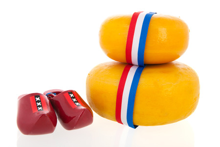 Two whole dutch cheeses with wooden clogs isolated over white  photo