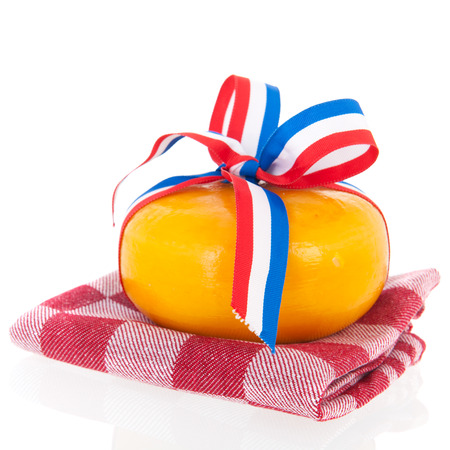 Two whole dutch cheeses with ribbon in flag colors on checked napkin isolated over white background photo