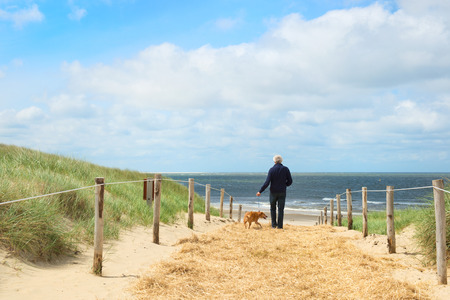 Coast from Nordsea at Dutch wadden island Texel with man and dog
