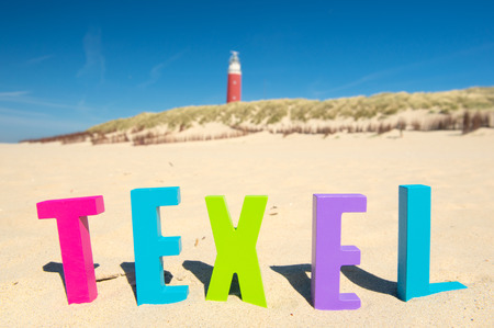 texel: Word Texel in front of the red lighthouse at Dutch wadden island