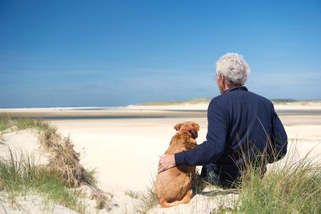 vacanza al mare: Uomo seduto con il cane sulla duna di sabbia in spiaggia olandese di Wadden sull'isola di Texel
